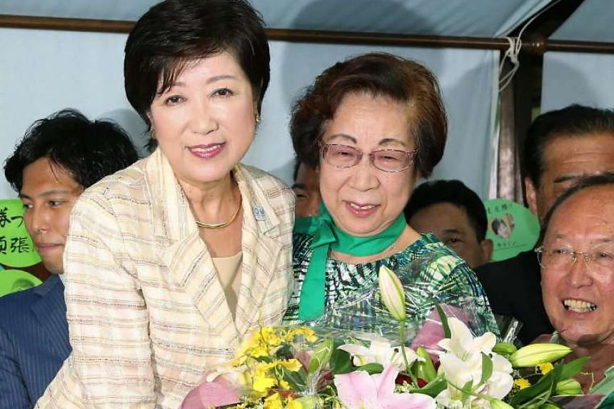 Former Japanese defence minister Yuriko Koike (left) celebrates her win as Tokyo governor, in Tokyo on July 31, 2016.