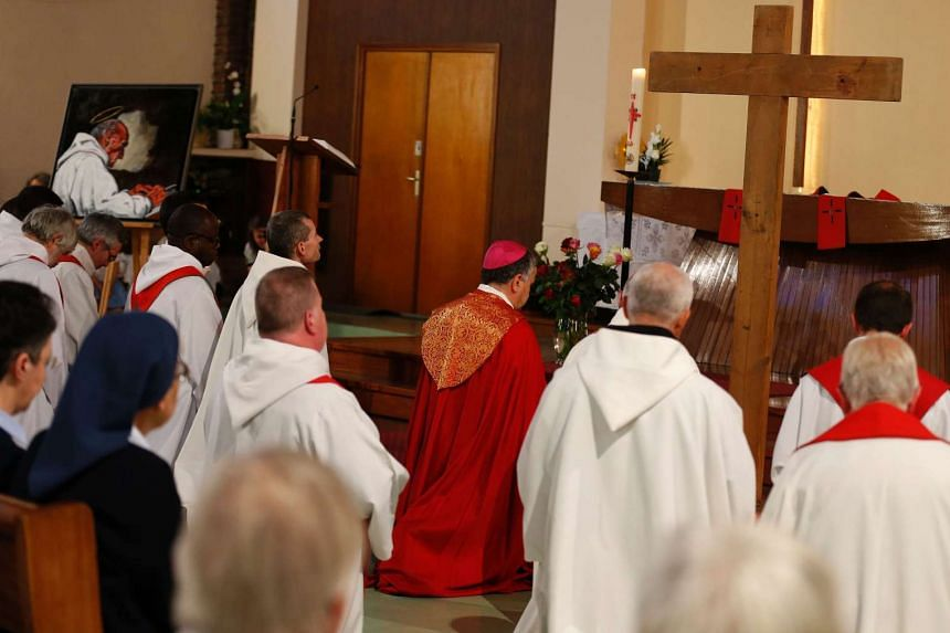 Clergymen pray next to a painting depicting French Priest Jacques Hamel, during a vigil at the church of Sainte-Therese in Saint-Etienne-du-Rouvray, on July 30, 2016.