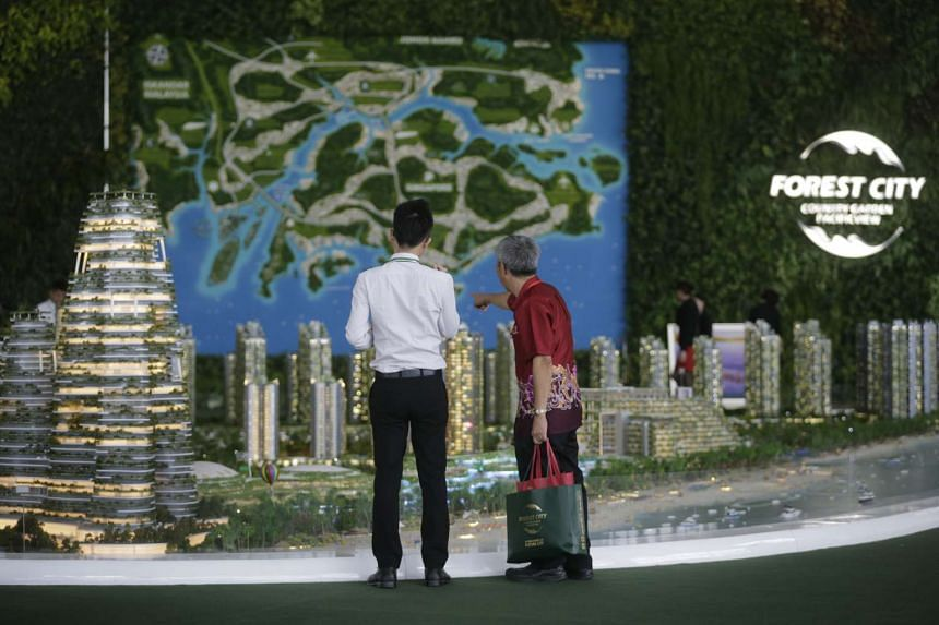 A potential buyer (right) with a sales representative looking at the model of Forest City in the Strait of Johor.