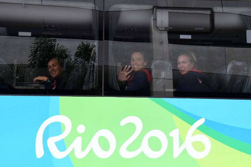 Athletes from Russia Olympic team wave from a bus to locals after their arrival to Antonio Carlos Jobim International Airport in Rio de Janeiro on July 29, 2016.