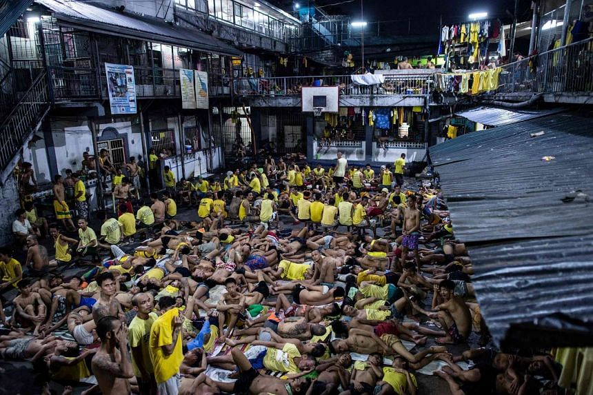 Inmates sleep on the ground of an open basketball court inside the Quezon City jail at night in Manila in this picture taken on July 21, 2016.