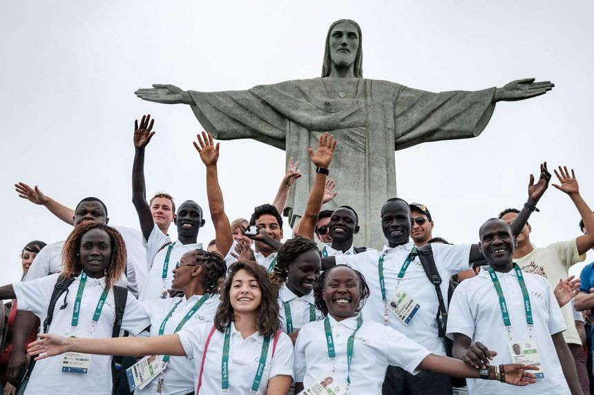 Athletes of the Refugee Olympic Team take pictures with a staff member in front of the statue of Christ the Redeemer.