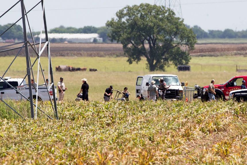The partial frame of a hot air balloon is visible above a crop field as investigators comb the wreckage of a Saturday morning accident that left 16 people feared dead.