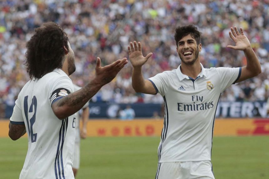 Marcelo celebrates with team mates after scoring a goal for Real Madrid.