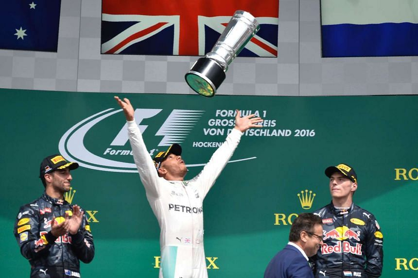 Lewis Hamilton (centre) throws the trophy after winning, next to second placed Daniel Ricciardo (left) and Max Verstappen (right) at the Hockenheim circuit, southern Germany, on July 31, 2016.