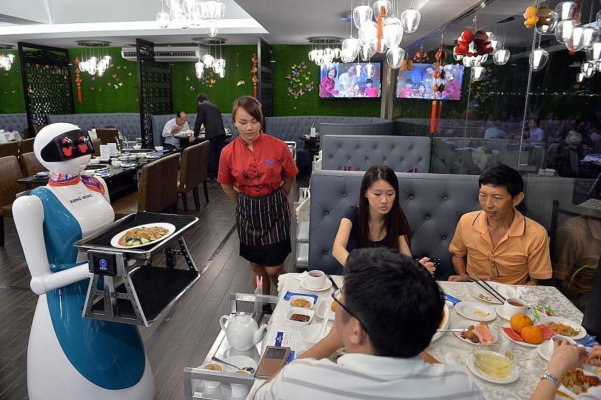 Robot Lucy delivering a dish at Rong Heng Seafood restaurant at East Coast Seafood Centre. When it arrives at the table, a human staff member transfers the dish to the table. The restaurant owners are using robots to deal with the manpower shortage.