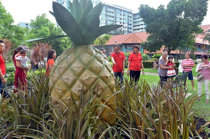 The giant pineapple sculpture that Nee Soon GRC MP Lee Bee Wah (in red and black) is looking at is part of a new art trail in Yishun which was launched yesterday. To her right is Nee Soon South Citizens Consultative Committee chairman Alex Lee. The 1