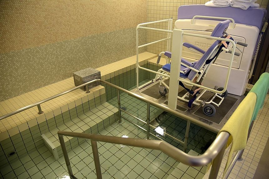 Madoka Kawaguchi residents who use wheelchairs can still enjoy a soak - an important part of the Japanese lifestyle. The platform on this machine is lowered with the wheelchair on top into the bath. At the suggestion of a resident at Ginmokusei Nishi