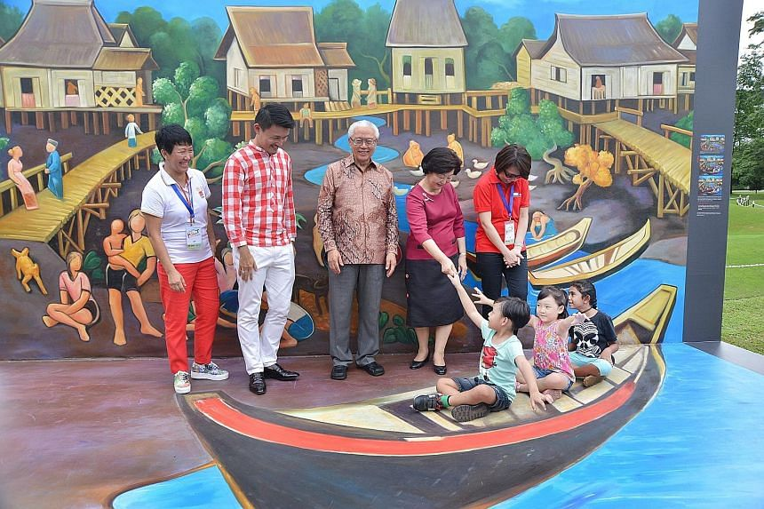 """Three children in the same """"boat"""" found themselves sharing the frame with President Tony Tan Keng Yam and his wife, Mary, in a photo booth at the Istana yesterday. Nuh Adam, five, Joan Ho, four and Zeenathunnisa, eight, were among the more than 15,00"""