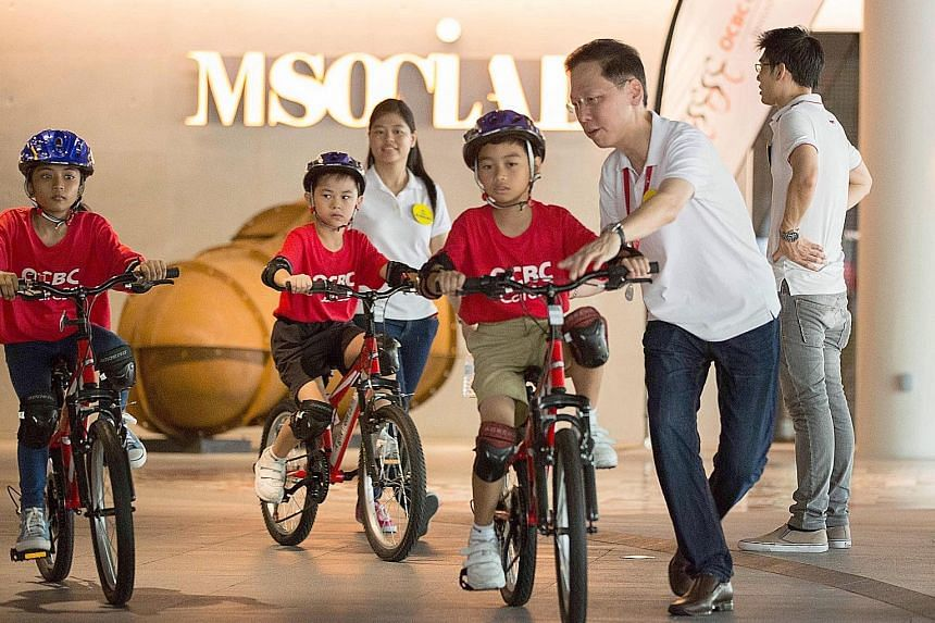 M Social general manager Ting Huong Tak (right) helping 10-year-old Abdul Hadi learn how to cycle yesterday, as part of OCBC Cycle's Teach A Child To Cycle programme conducted by staff volunteers from Millennium Hotels and Resorts at M Social Singapo