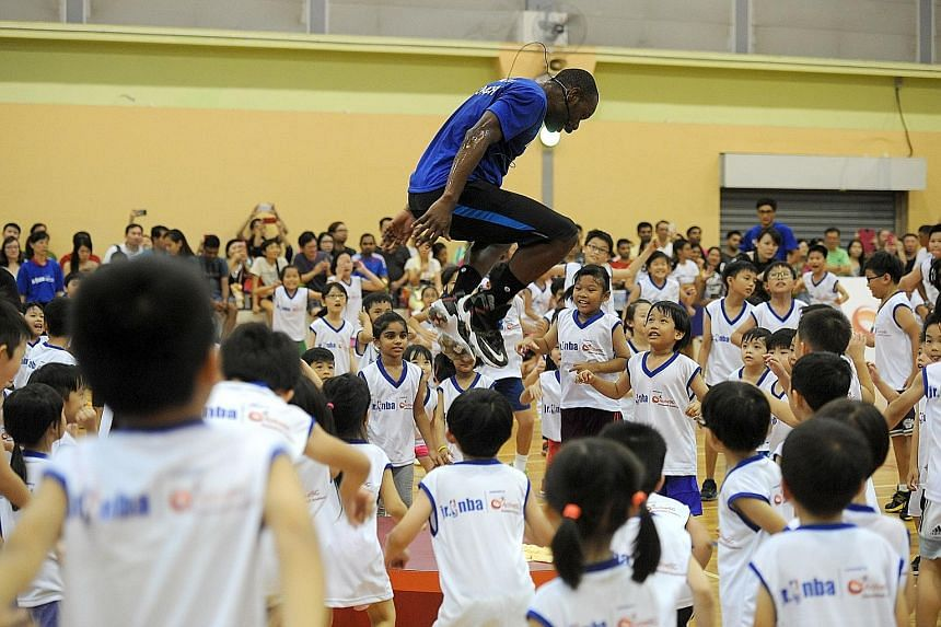 Jr NBA coach Chris Sumner (centre) jumps during a training session organised by ActiveSG Basketball Academy at the Sengkang Sports Hall. The free two-hour clinic was open to kids between five and 14 years old.