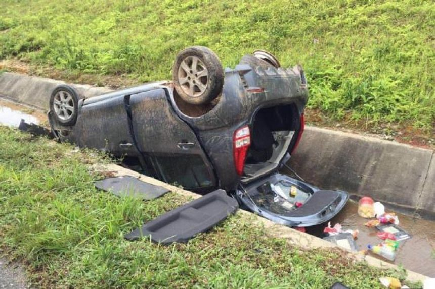 A Perodua Myvi carrying a Singapore family of three turned turtle in a drain after swerving to avoid a water puddle on the expressway.