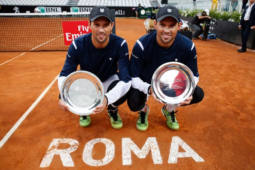 Bob and Mike Bryan pose with their trophies after winning the doubles final in Rome on May 15, 2016.