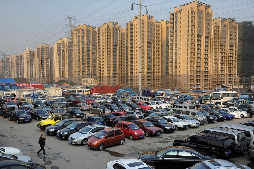 Car dealers and customers walk at a second-hand car market near a newly-built residential area in Hefei, Anhui province, China in 2013.