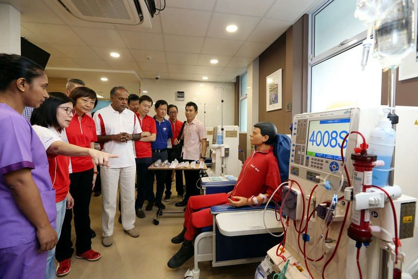 Staff showing Home Affairs and Law Minister K. Shanmugam (in white) and Nee Soon GRC grassroots adviser Lee Bee Wah (third from left) around the new dialysis centre at Nee Soon South, on July 31, 2016.