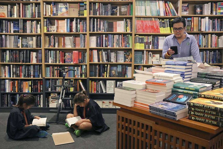 A pair of young fans reading their copies of the latest Harry Potter book in Kinokuniya.