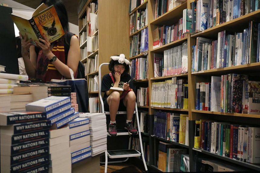 A young fan of the Harry Potter books reading her copy at Kinokuniya.