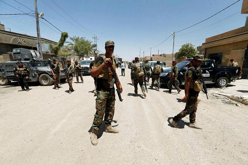 Iraqi government forces gather in Falluja after recapturing the city from Islamic State militants, Iraq on July 1.