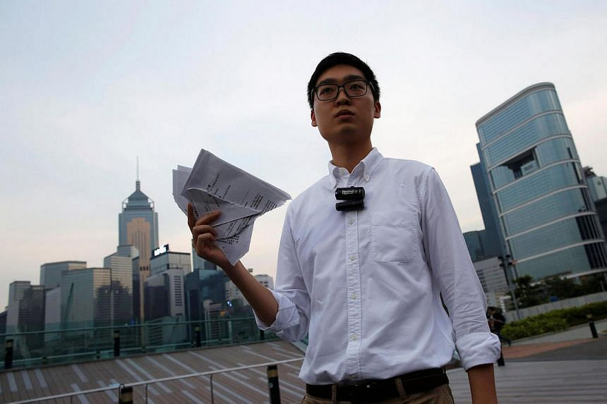 """Pro-independence Hong Kong National Party convenor Chan Ho Tin holds a form saying the city is an """"inalienable"""" part of China, after being disqualified from running in Legislative Council elections in Hong Kong, China on July 30."""
