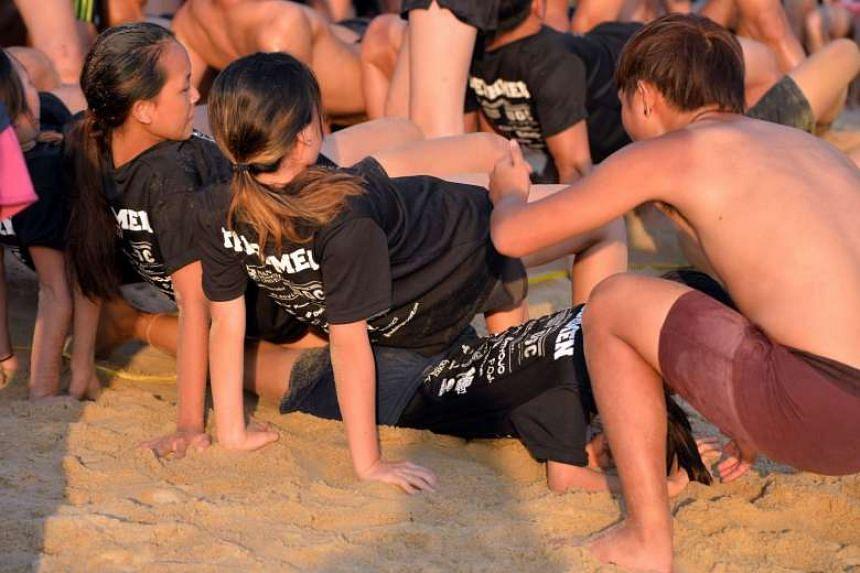 University students taking part in orientation games at Siloso Beach on Sentosa on Friday.
