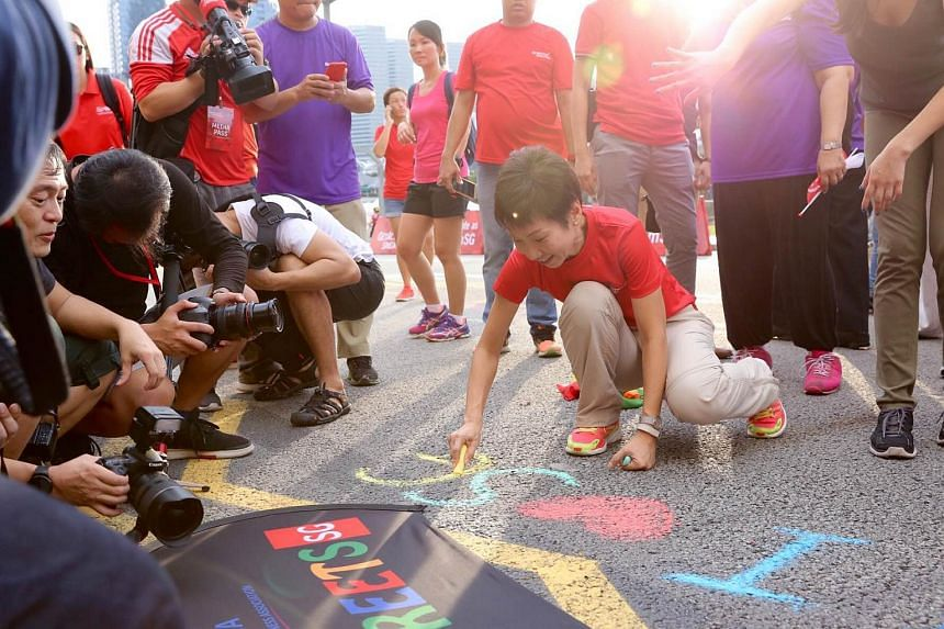 """Minister Grace Fu writing """"I Love SG"""" with a chalk on the tar road."""