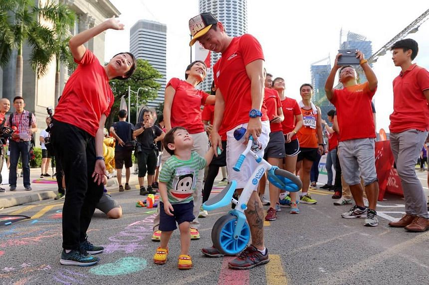 Two-year-old Lincoln Lieu in awe of the flying drone above. With him is his father, para sprinter Lieu Teck Hua, 36, Dr Teo-Koh Sock Miang, President of the Singapore Disability Sports Council (on his left), and Minister Grace Fu (at the back).