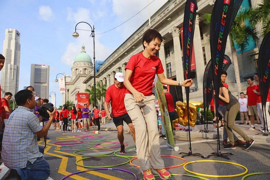 Minister for Culture, Community and Youth Grace Fu hopping in between the mini hoops, at a games station that the public can take part in.