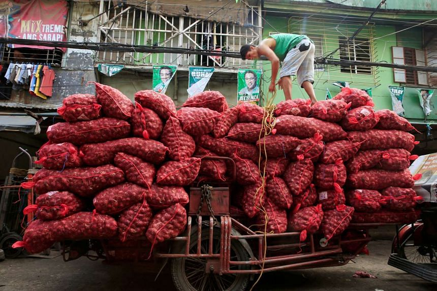 A worker stands on top of piles of red onion sacks as he prepares to deliver the produce to a warehouse in Manila, on July 4, 2016.