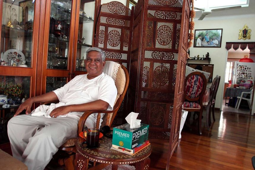 President Nathan resting at his home after his morning exercise, with his favourite bittergourd tea on the table. A family photo hangs on the wall in the background.