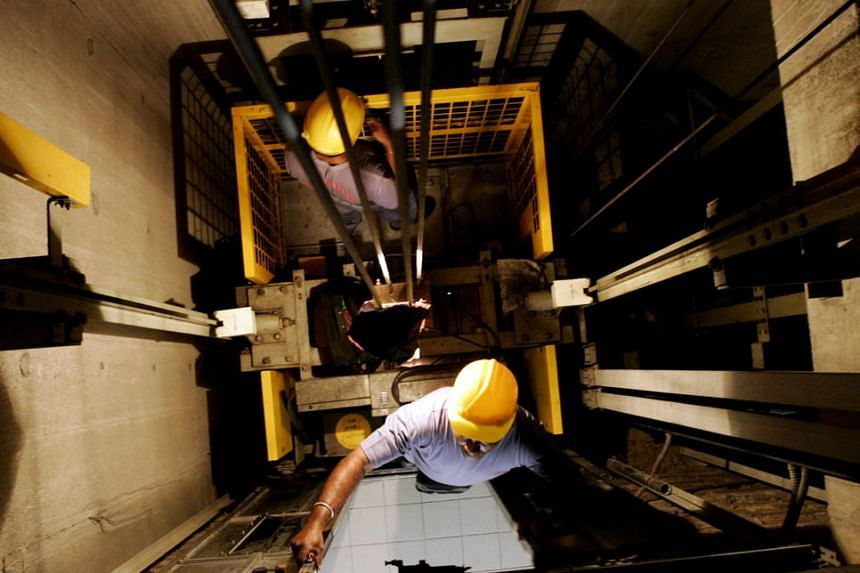 Technicians seen servicing a lift in a lift shaft at a block of HDB flat in Hougang in 2005.