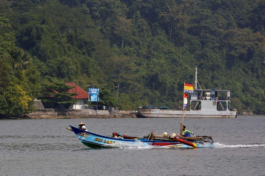 A fishing boat motors past the ferry port on the prison island of Nusa Kambangan island in Cilacap, Central Java, on July 28, 2016.
