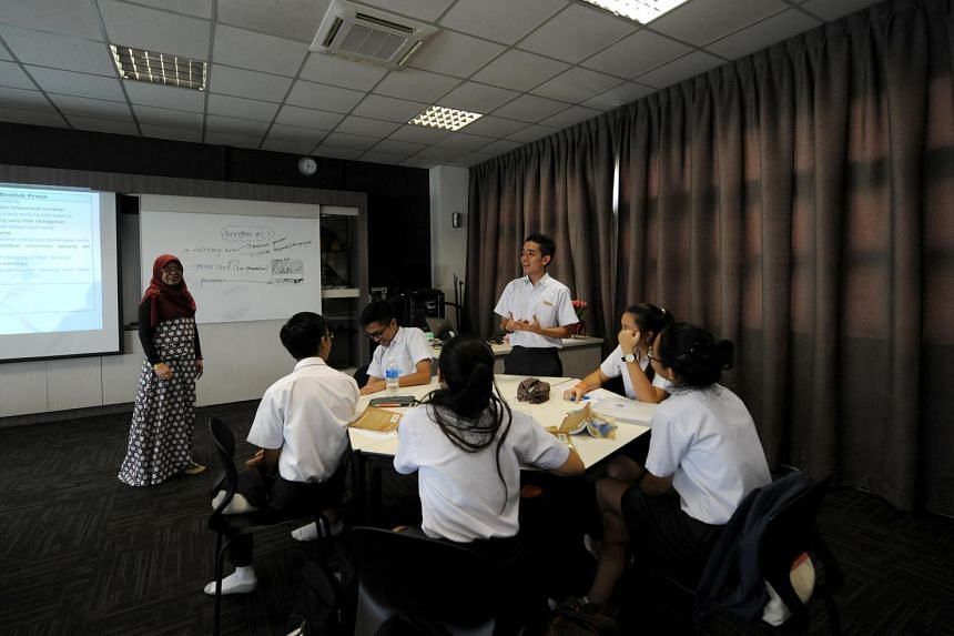Mdm Zainun Hashim (extreme left), a senior teacher and coordinator for the Malay Language Elective Programme, engaging her students in her Malay Literature class.