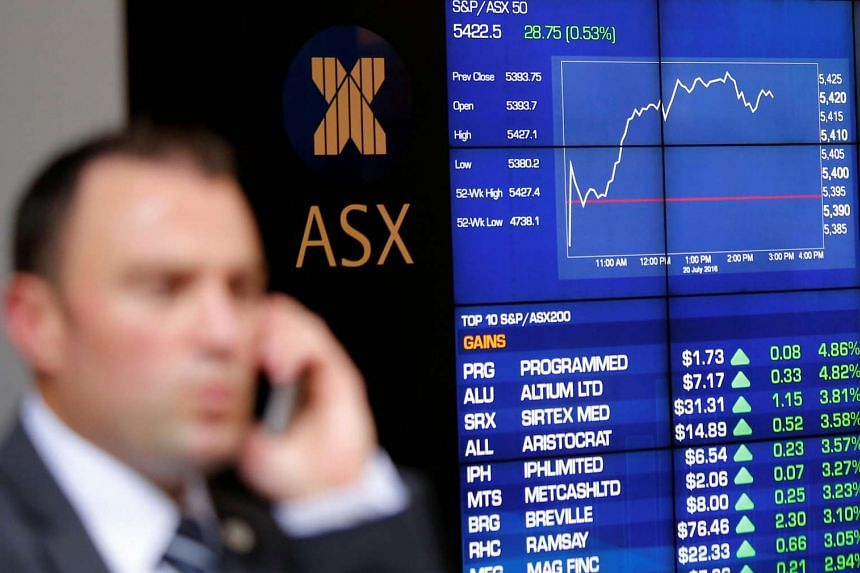 An investor reacts as he talks on his phone in front of a board displaying stock prices at the Australian Securities Exchange (ASX) in Sydney, Australia on July 20.