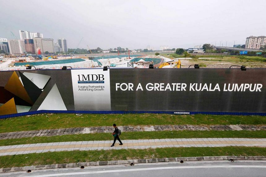 A man walks past a 1MDB billboard at the funds flagship Tun Razak Exchange development in Kuala Lumpur, on March 1, 2015.