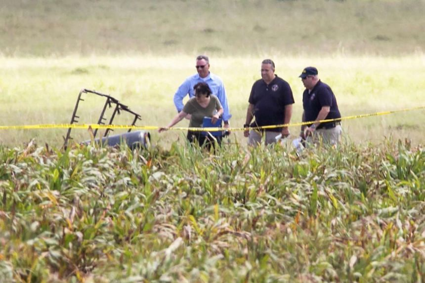 The partial frame of a hot air balloon is visible above a crop field as investigators comb the wreckage that left 16 people feared dead when the balloon crashed in Maxwell, Texas, July 30.
