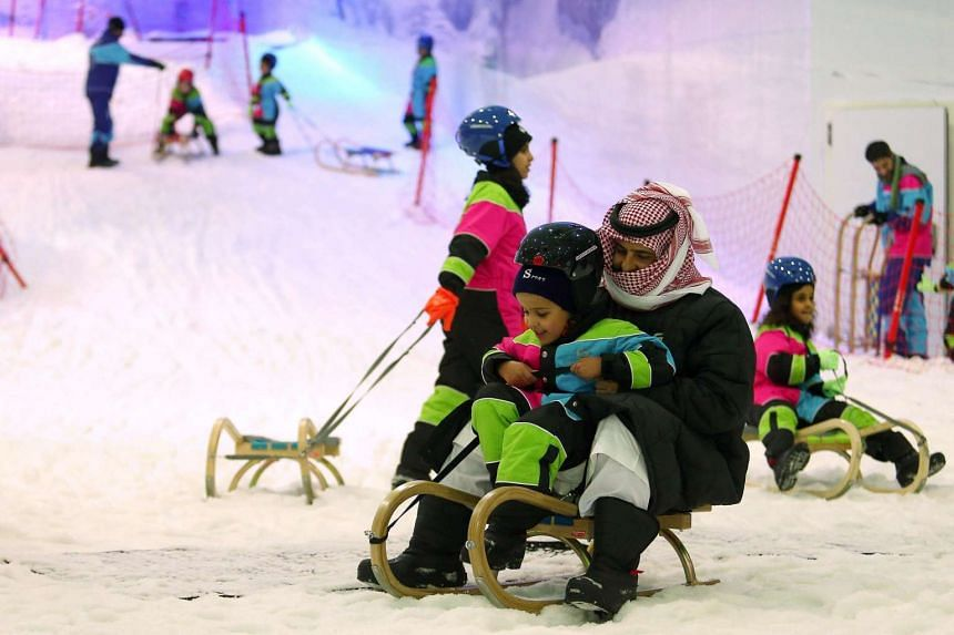 Saudi man and a boy sliding on a sledge at the indoor snow theme park 'Snow City' in the Al-Othaim Mall Rabwa in the capital Riyadh on July 20.