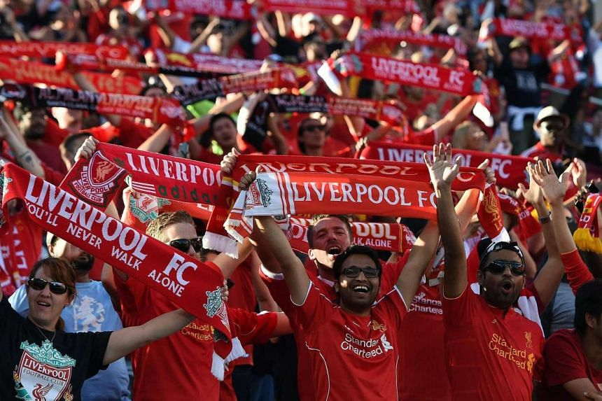 Liverpool fans cheer as they hold up banners during the International Champions Cup football match against AC Milan at Levi's Stadium in Santa Clara, California on July 30.