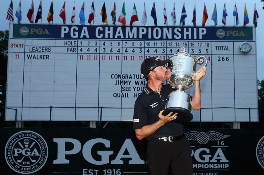Jimmy Walker celebrates with the Wanamaker tophy in front of the leaderboard after winning the 2016 PGA Championship on July 31, 2016, in Springfield, New Jersey.