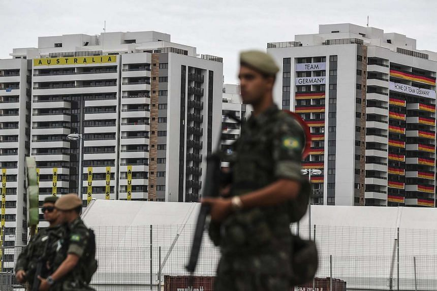 Members of the Brazilian Army stand guard outside the accommodation buildings of the delegations of Australia and Germany at the Olympic Village in Rio de Janeiro on July 26, 2016.