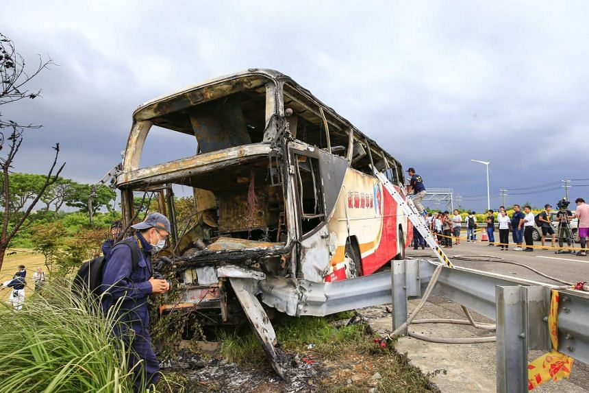 Taiwanese investigators conduct investigations after a tourist bus crashed and burned in Taoyuan, on July 19, 2016.