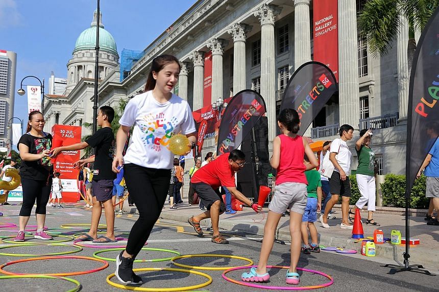 Singapore Wellness Association volunteers Damiel Ang (in black), 14, and Poh Wen Lin (in white, foreground), 19, facilitating street games in front of the National Gallery Singapore yesterday as part of the activities during the GetActive! Singapore