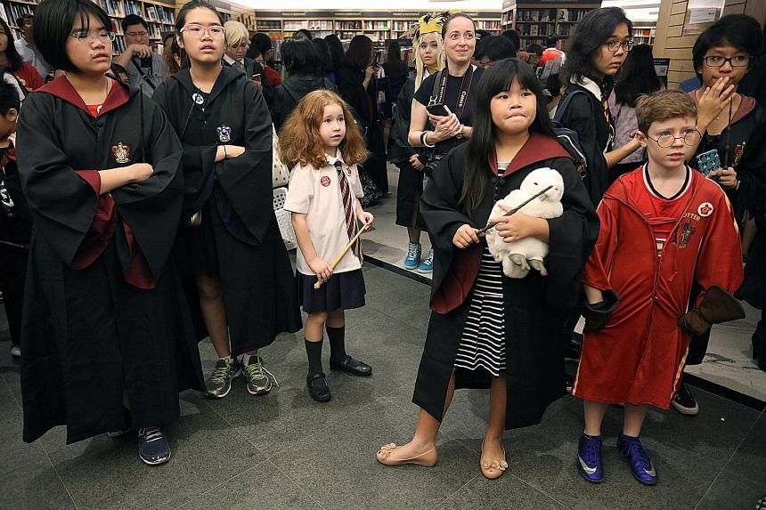 Fans of the Harry Potter series waiting to take part in a cosplay event at Books Kinokuniya yesterday. Major bookstores here opened at 7.01am to coincide with the international release of Harry Potter And The Cursed Child Parts I and II, the script f