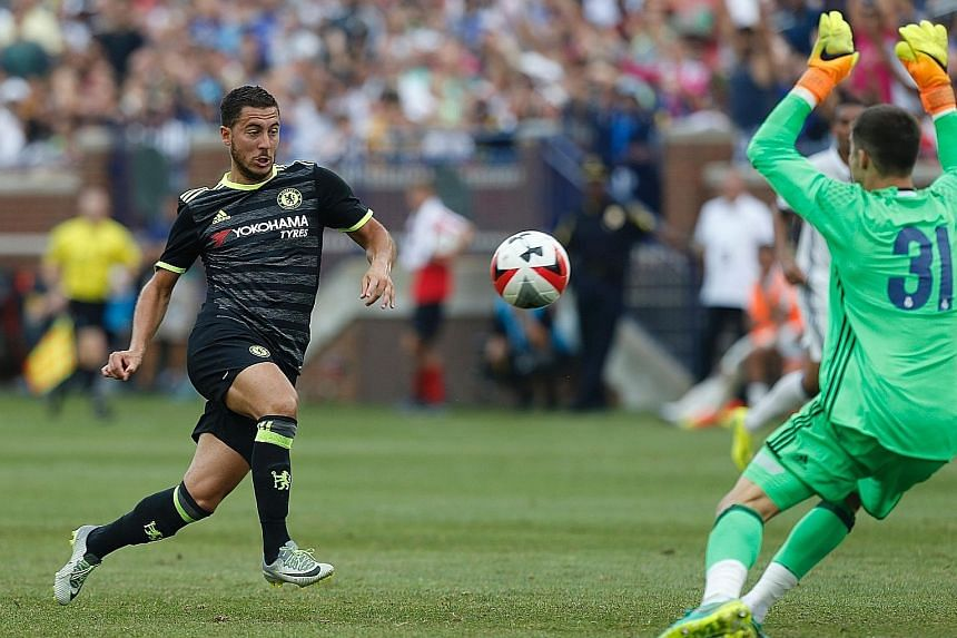 Chelsea forward Eden Hazard (left) shoots and scores against Real Madrid goalkeeper Ruben Yanez during an International Champions Cup friendly loss in Ann Arbor, Michigan. The Belgium international admits that Chelsea are tired after a week of manage
