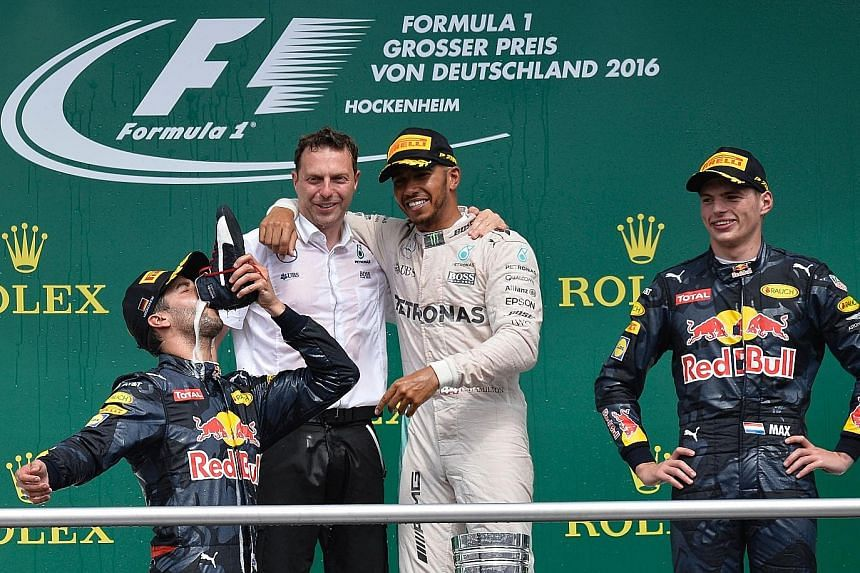 German Grand Prix winner Lewis Hamilton (white overalls) watches on as Daniel Ricciardo drinks champagne out of a shoe beside his Red Bull team-mate Max Verstappen.