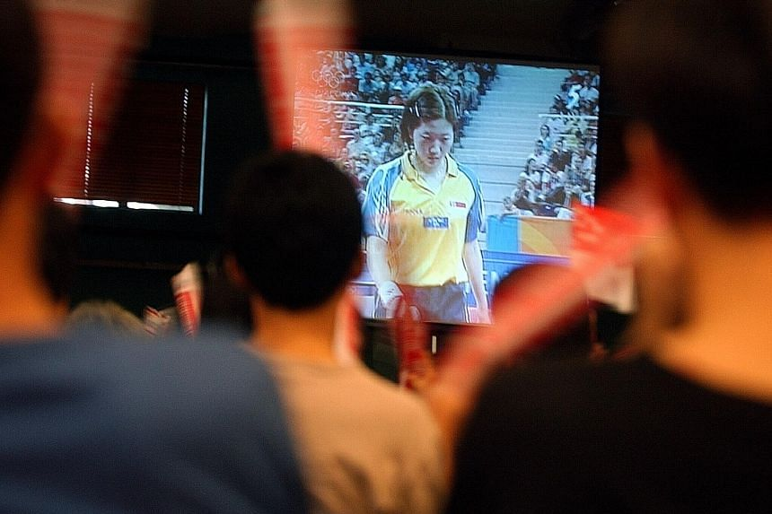 A crowd in Singapore watching as Li Jiawei attempts to win a table tennis bronze medal at the 2004 Athens Games. This month, Singaporeans will not be able to watch their compatriots compete 'live' at the Rio Games.