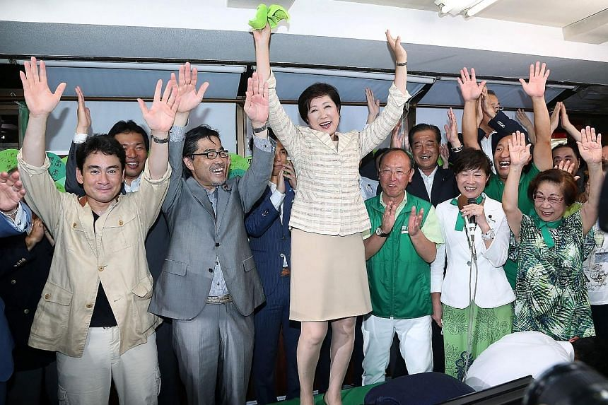 Ms Koike (centre) and her supporters celebrating her win as Tokyo governor, in Tokyo, yesterday. Visibly moved, her voice cracked as she alluded to shattering a glass ceiling in a country that traditionally ranks low in gender equality indices. One o