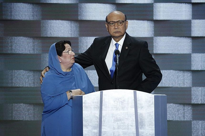Mrs Khan on stage at the Democratic National Convention with her husband. Her silence was taken by Mr Trump as a sign of subservience.