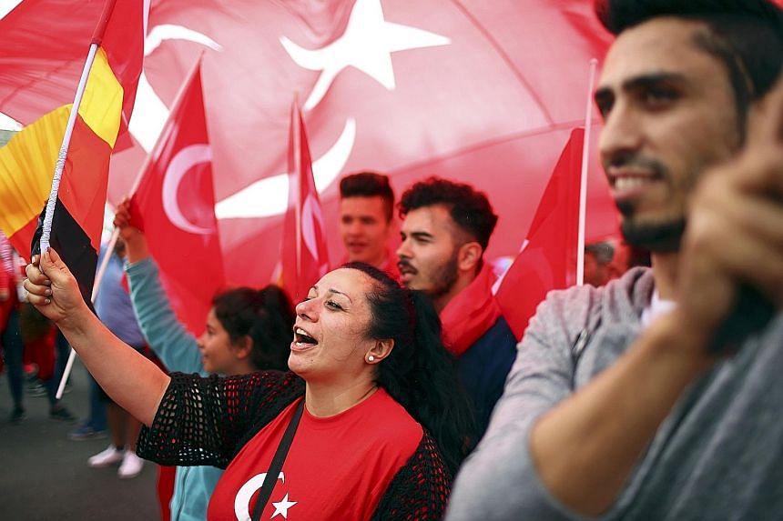 Supporters of Turkey's President Erdogan waving Turkish flags during a pro- government protest in the Germany city of Cologne yesterday.