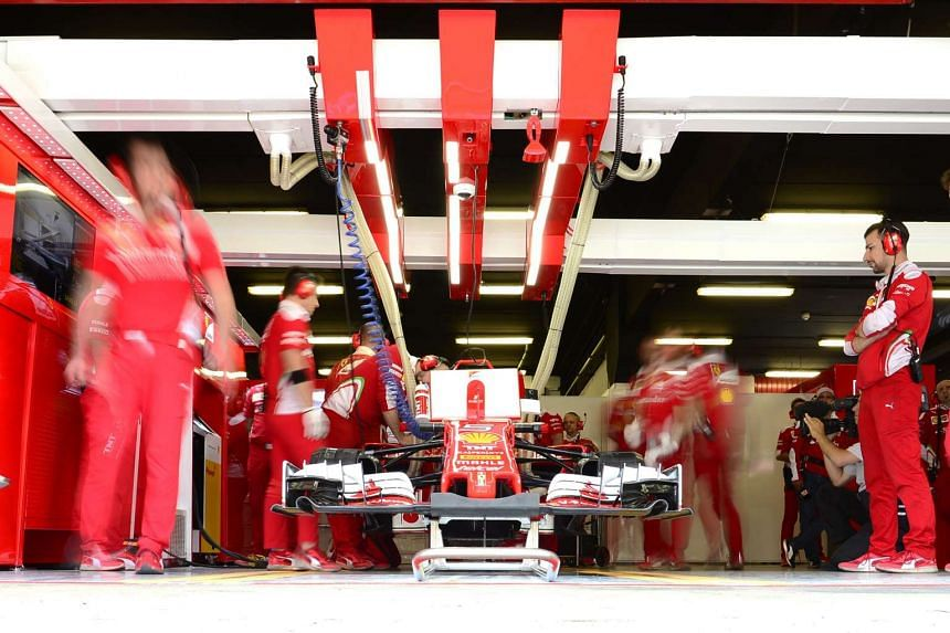 Mechanics work on the car of Ferrari's German driver Sebastian Vettel in the pits. Vettel has vowed to return stronger after a disappointing race. Copyright: AFP