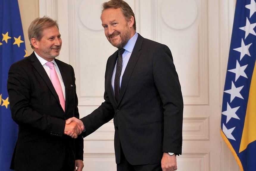 Chairman of Bosnia and Herzegovina's tripartite presidency, Bakir Izetbegovic, shakes hands as he welcomes European Union Commissioner for Enlargement and Neighborhood policy, Johannes Hahn, in Sarajevo during an official visit on June 15, 2016,
